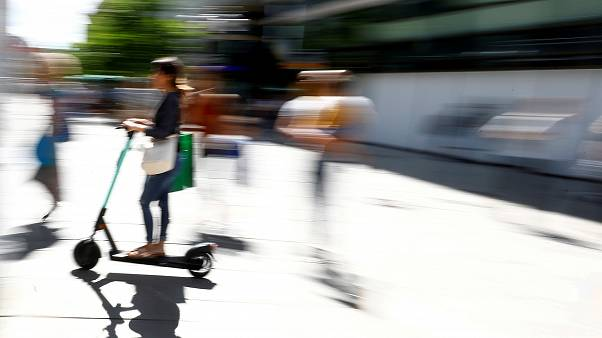 A young woman rides an e-scooter through a pedestrian area in Frankfurt