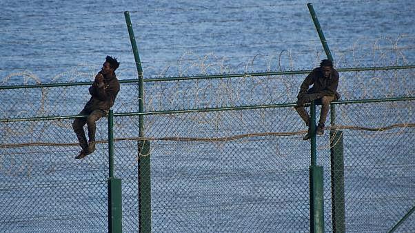 مهاجران من إفريقيا يحاولان ��بور السياج الذي يفصل سبتة الإسبانية عن المغرب