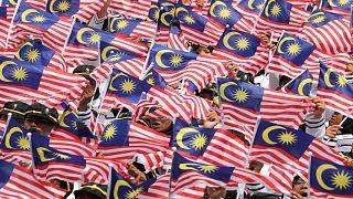 ماليزيون يرفعون علم بلادهم خلال الاحتفال بالذكرى 62 لاستقلال البلاد يوم 2019/08/31. ليم هواي تانغ/رويترز