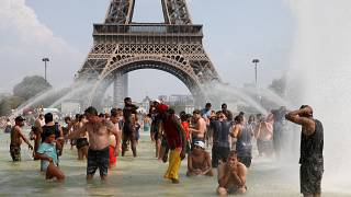 eople cool off in the Trocadero fountains across from the Eiffel Tower in Paris as a new heatwave broke temperature records in France, July 25, 2019.