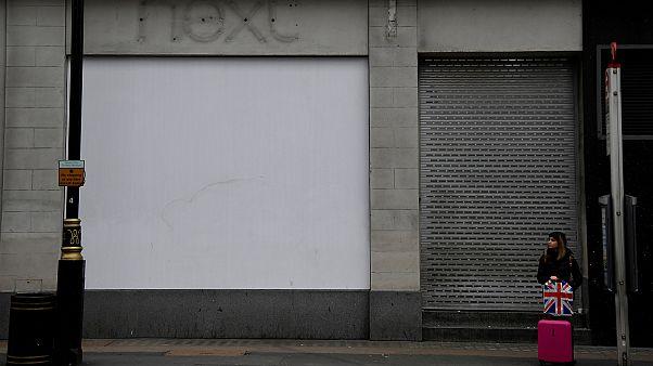Bezárt londoni bolt előtt buszra várakozó utas