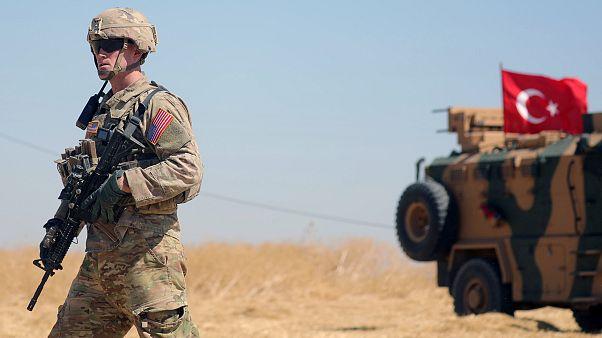 جندي تابع للقوات الأميركية أمام آلية للجيش التركي في الشمال السوري
