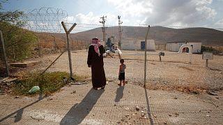 فلسطينيون يقفون إلى جانب السياج في وادي الأردن في الضفة الغربية المحتلة
