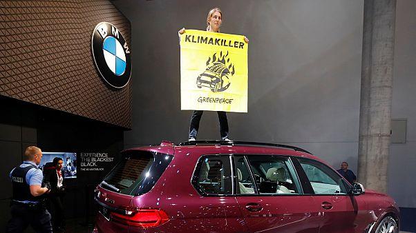 """نشاطة """"السلام الأخضر"""" تعتلي سيارة بي إم دبليو رباعية الدفع احتجاجا على تأثيرها السلبي على المناخ"""