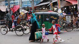 امرأة مع أطفال تعبر طريقًا في دكا-بنغلاديش