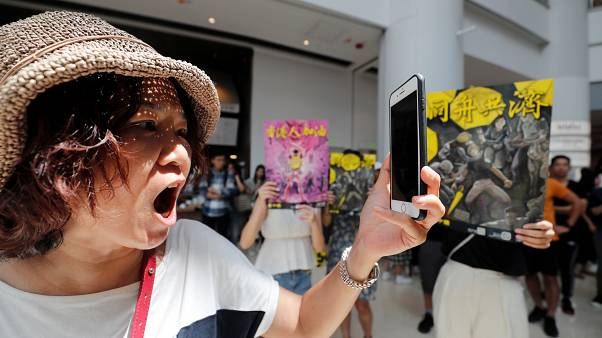 A woman reacts near anti-government supporters at Olympian City 2 shopping mall in Hong Kong, China, September 13, 2019.