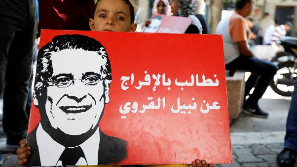 A boy holds a picture of presidential candidate Nabil Karoui as he takes part in a rally asking for his release from prison, in front of the courthouse in Tunis, Tunisia,