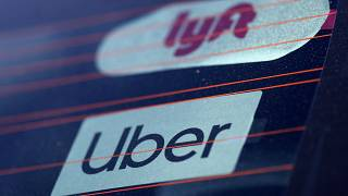 Uber and Lyft signs are seen on a car in Redondo Beach