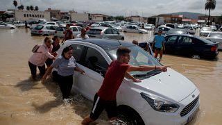 أناس يدفعون سيارة داخل مرآب غمرته مياه الفيضان في أوريولا الإسبانية. 2019/09/13. جون نازا - رويترز
