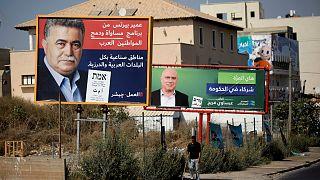لافتة انتخابية لحزب العمال تصور زعيم الحزب عمير بيرتس بجانب لافتة أخرى للانتخابات الكنيست في إسرائيل