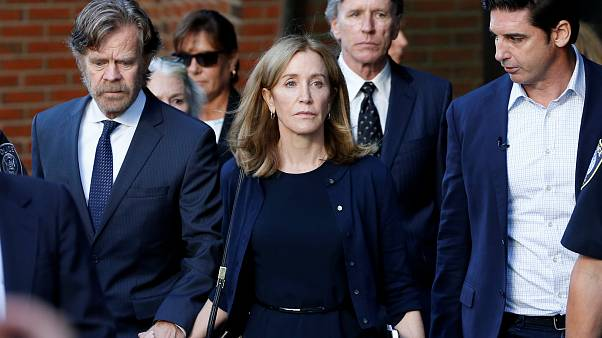 Actress Felicity Huffman leaves court with her husband William H. Macy (left)