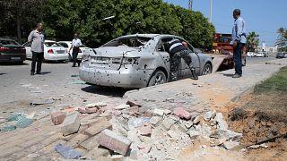 شرطي يعاين سيارة تعرضت لشظايا قصف استهدف مطار معيتيقة يوم 2019/08/24. حازم أحمد - رويترز
