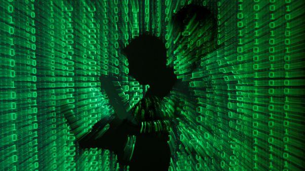 اللغة الرقمية مسقطة على رجل يحمل جهاز كمبيوتر، في مكتب في وارسو في 24 يونيو 2013