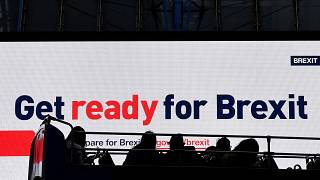 A bus passes an electronic billboard displaying a British government Brexit information awareness campaign advertisement in London, Britain