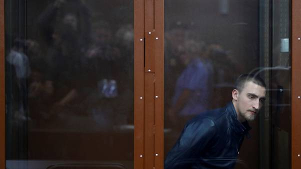 Pavel Ustinov, ammanettato, attende la sentenza. Sarà dura: 3 anni e mezzo di carcere.