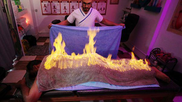 ماساژور مصری با «حوله آتشین» دردهای عضلانی را تسکین میدهد