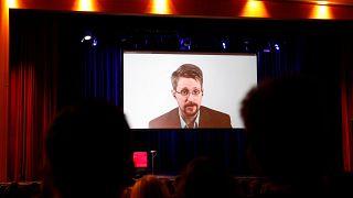 """إدوارد سنودن متحدثاً إلى الحضور عبر شاشة عملاقة خلال إطلاق كتابه """"سجل دائم"""" في ألمانيا اليوم"""