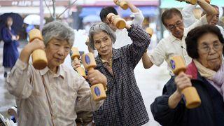 Idős japánok fa súlyzókkal tornáznak az idősek tiszteletének országos napján tartott köztéri rendezvények egyikén Tokióban 2019. szeptember 16-án