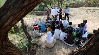 تلاميذ يمنيون في حصة مدرسية تحت شجرة في محافظة تعز