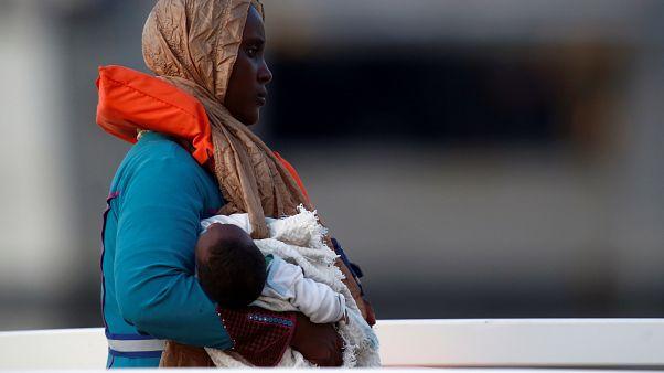 مهاجرة تحمل رضيعاً خلال وصولها إلى أحد موانئ مالطا بعد إنقاذها من قبل القوات البحرية
