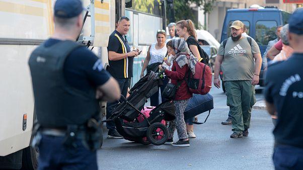 Αστυνομικοί οδηγούν αλλοδαπούς σε λεωφορεία κατά τη διάκεια εκκένωσης κτιρίων, όπου τελούσαν υπό κατάληψη, από το 2016