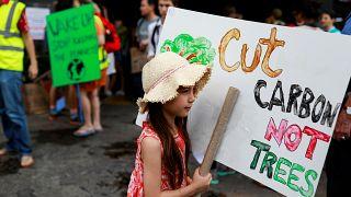 Corten el CO2, no los árboles, dice el cartel de esta niña en Tailandia