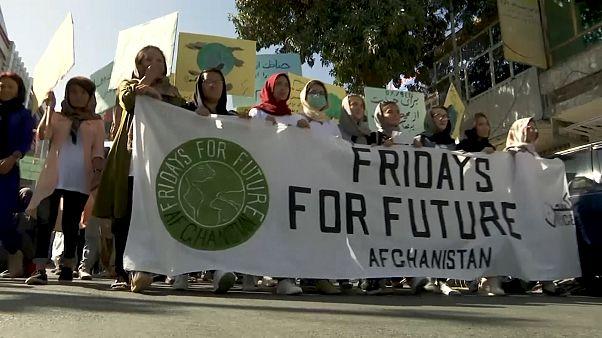 Afgan gençler güvenlik güçlerinin korumasında iklim için sokağa çıktı