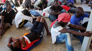 Migrants are seen after being rescued by Libyan coast guard in Khoms in August