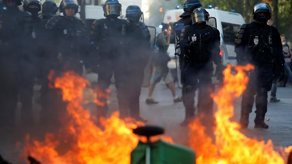 Riot police officers stand next to a burning barricade during a protest urging authorities to take emergency measures against climate change, in Paris, France.