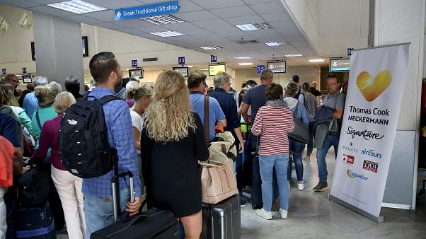 People line up in front of a counter of Thomas Cook at the Heraklion airport on the island of Crete, Greece September 23, 2019