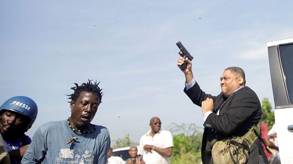 Senator Jean Marie Ralph Féthière (r.) schießt mit einer Pistole.