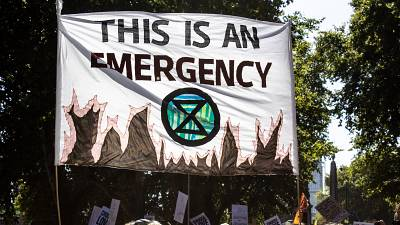 A banner declaring climate emergency alongside an Extinction Rebellion symbol is held high above the crowd