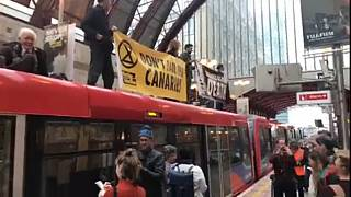 Extinction Rebellion activists protest on top of train at Canary Wharf