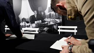 A man signs the book of condolences in front of Paris city hall to pay tribute to late former French President Jacques Chirac in Paris, France, September 26, 2019.