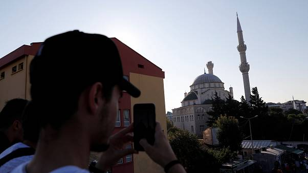 A man takes a picture of a damaged mosque in Istanbul following the earthquake