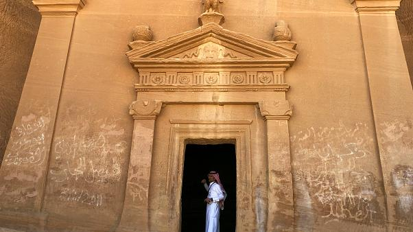 A tour guide stands inside a tomb at Madain Saleh
