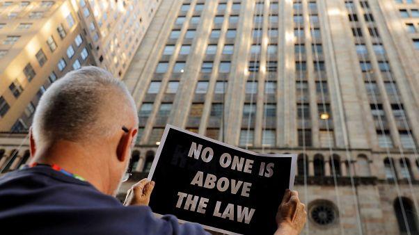 """متظاهر يحمل لافتة """"لا أحد فوق القانون"""" كجزء من مظاهرة لدعم جلسات سحب الثقة عن ترامب في نيويورك"""