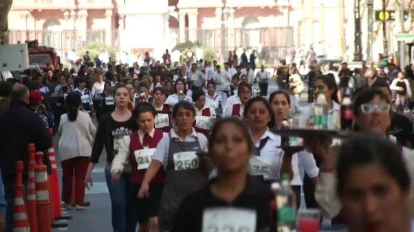 شاهد: نُدُل يتسابقون في الأرجنتين ببدلات العمل حاملين أطباقا وكؤوسا
