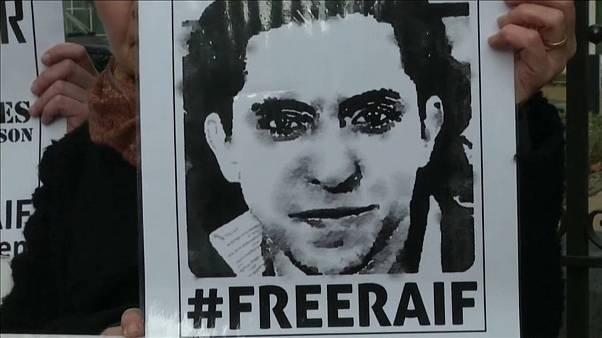 محتج يرفع ملصقاً مطالباً بإطلاق سراح المدون السعودي المسجون رائف بدوي