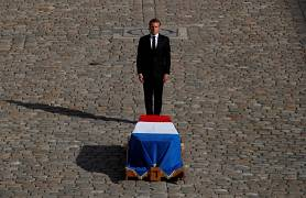 French President Emmanuel Macron stands in front of the flag-draped coffin of late French President Jacques Chirac during a military funeral honors ceremony