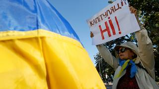 """A woman attends a rally against approval of so-called Steinmeier Formula, in Kiev, Ukraine October 2, 2019. A sign on a poster reads: """"No surrender!"""""""
