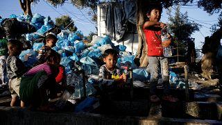 طفال يملئون الزجاجات بالمياه بجانب كومة من القمامة في مخيم مؤقت للاجئين والمهاجرين في جزيرة ليسبوس باليونان