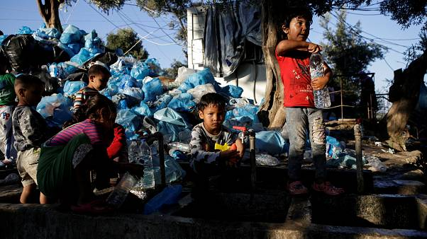 Children fill bottles with water next to a pile of garbage on the island of Lesbos