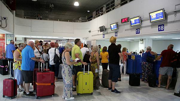 """مسافرون يصطفّون في طابور أمام مكاتب """"توماس كوك"""" في مطار هيراكليون باليونان"""