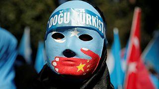 متظاهر يرتدي قناعًا يمثل أقلية الإيغور - أرشيف رويترز