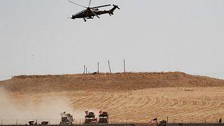 طائرة هليكوبتر عسكرية تركية مع القوات التركية والأميركية على الأرض خلال دورية مشتركة بين الولايات المتحدة وتركيا في شمال سوريا