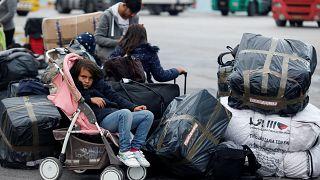 فتاة تجلس في عربة أطفال بينما ينتظر اللاجئون والمهاجرون نقلهم إلى مخيمات في ميناء بيرايوس في اليونان