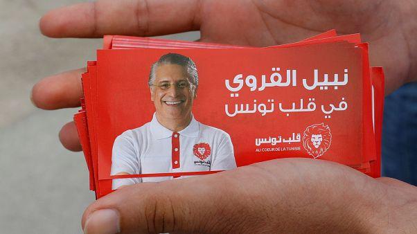 مواطن يحمل صور دعائية للمرشح الرئاسي التونسي نبيل القروي