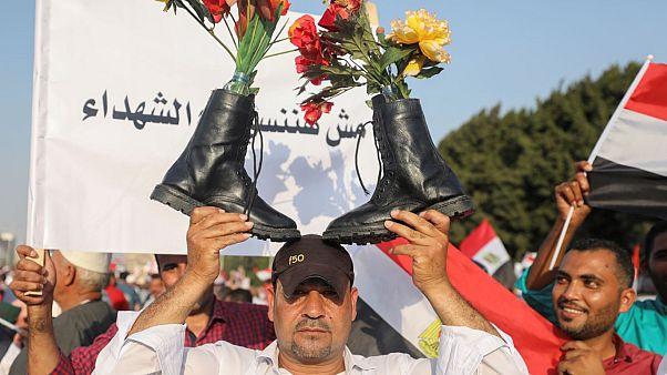 أحد أنصار الرئيس المصري عبد الفتاح السيسي يحمل أحذية عسكرية فوق رأسه وهو يهتف بالشعارات في القاهرة