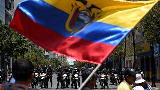 Demonstrators wave the national flag while facing riot police during protests against Ecuador's President Lenin Moreno's austerity measures